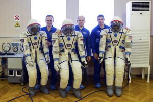 U.S. astronaut Michael Hopkins, Russian cosmonauts Oleg Kotov and Sergey Ryazanskiy pose for a picture at the Baikonur cosmodrome